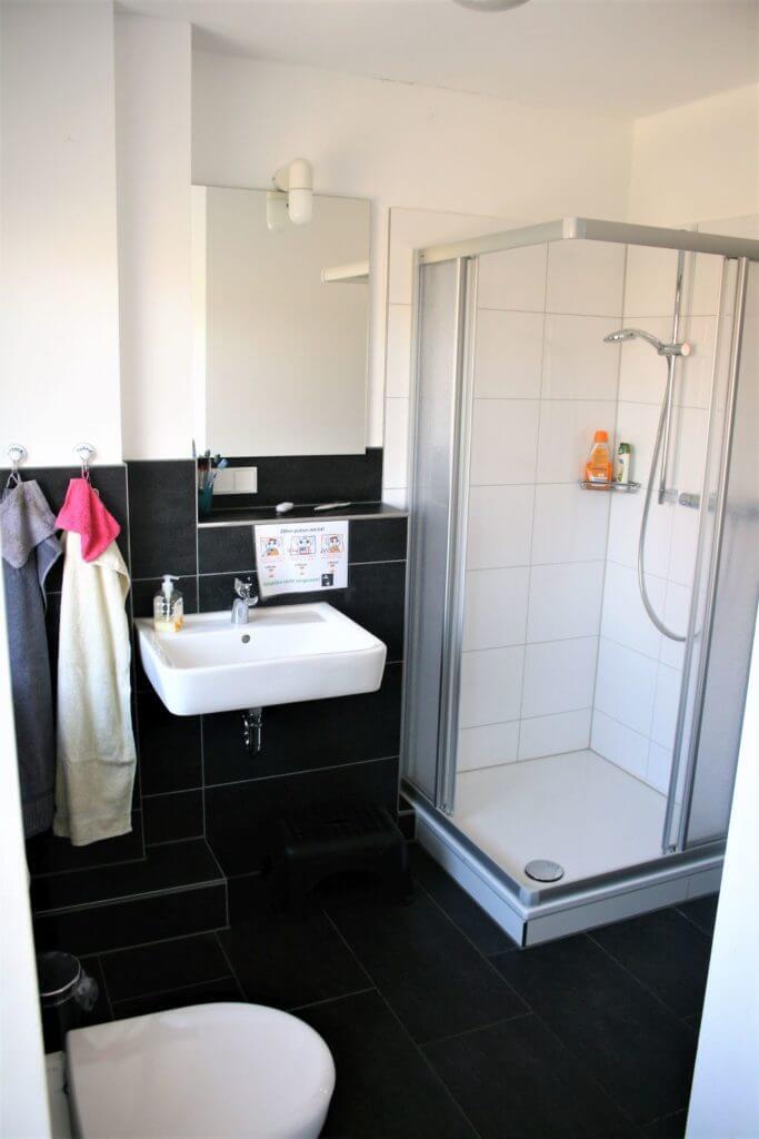 Ein helles, modernes Bad mit schwarzen Fliesen und weißen Wänden mit Dusche, Waschbecken und Toilette