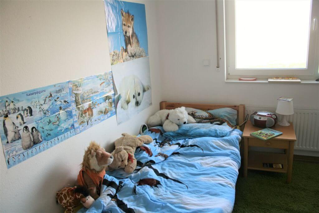 Ein Kinderbett mit Kuscheltieren und Tierposter an der Wand