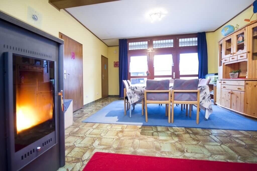 Wohnbereich mit Tisch und Stühlen und angezündete Kamin