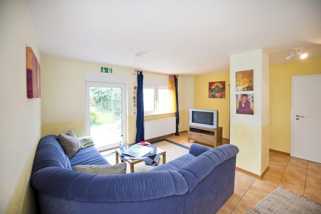Wohnbereich mit großem blauen Ecksofa und Fernseher
