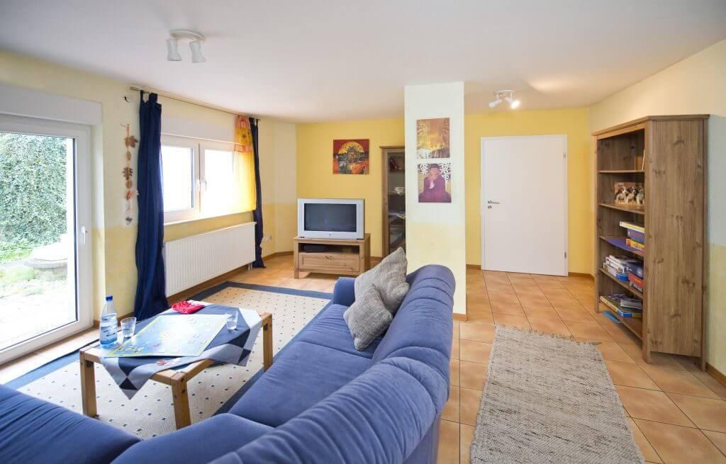 Wohnbereich mit großem blauen Ecksofa, Fernseher und Spieleregal