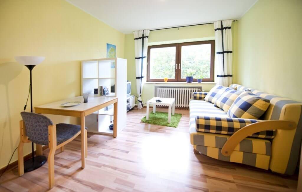 Hellgelb gestrichenes Zimmer mit großem Sofa und Fernseher und Esstisch