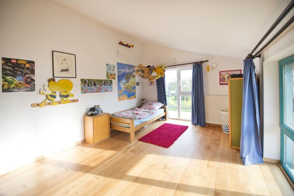 Helles freundliches Zimmer mit Bett, Schrank und Kuscheltierhängematte