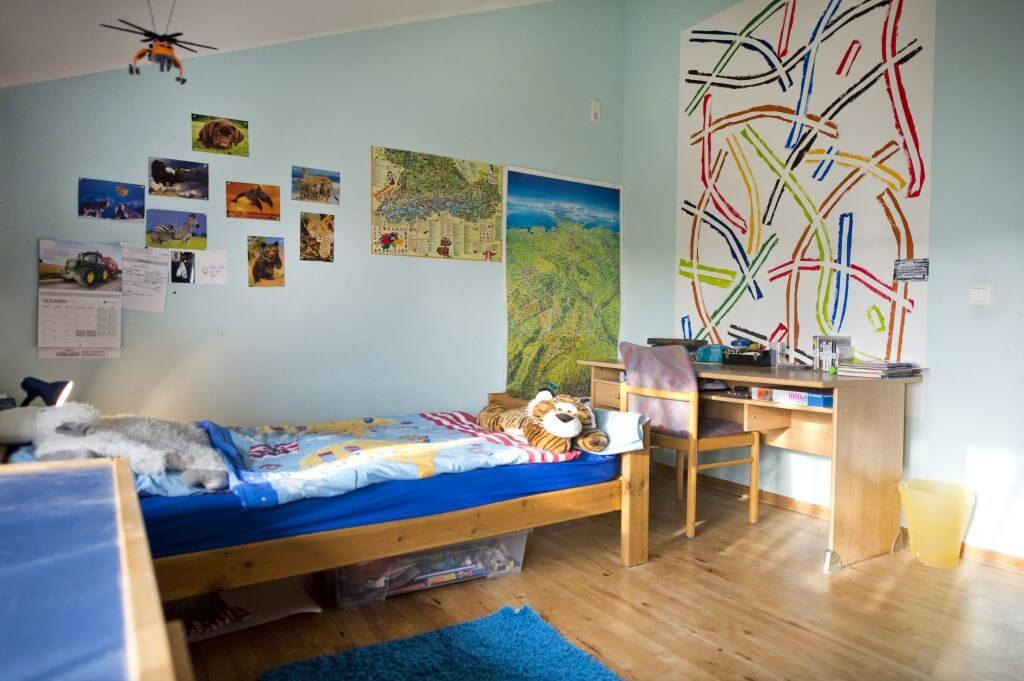 Zimmer in der Wohngruppe Wimmer mit Bett, Schreibtisch und Tierbildern und Landkarten an der Wand