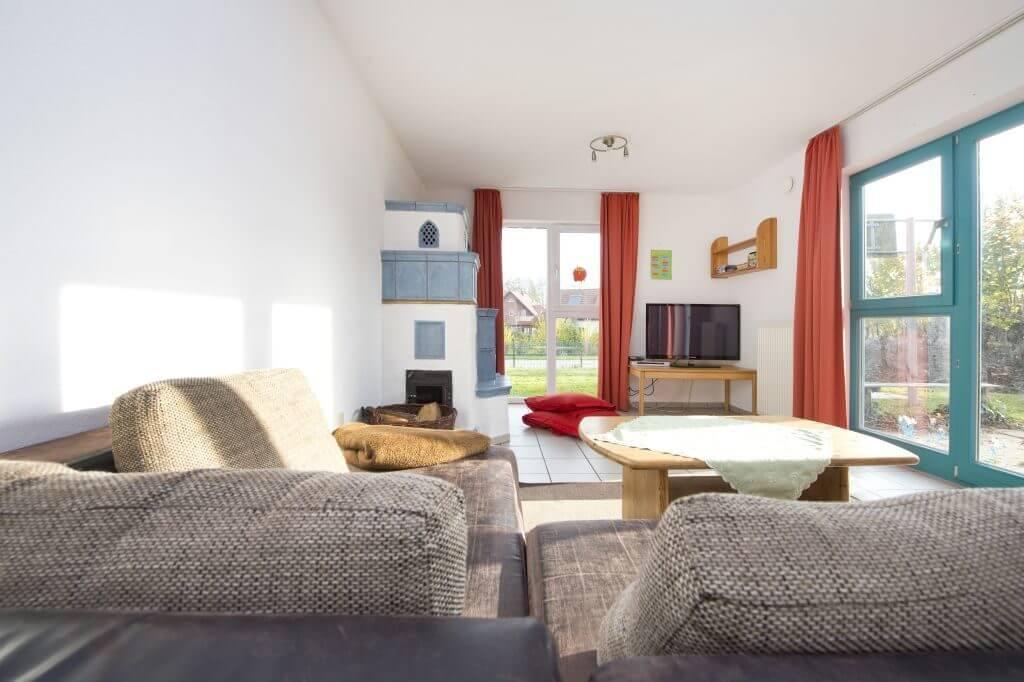 Wohnbereich der Wohngruppe Wimmer mit braunem Sofa, viel Tageslicht, einem Fernseher in der Ecke und einem blau gefliesten Kaminofen