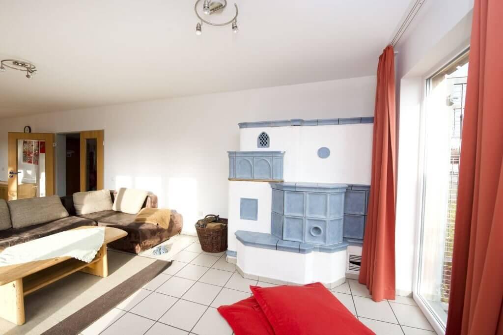 Wohnbereich der Wohngruppe Wimmer mit hellblau gefliestem Kaminofen