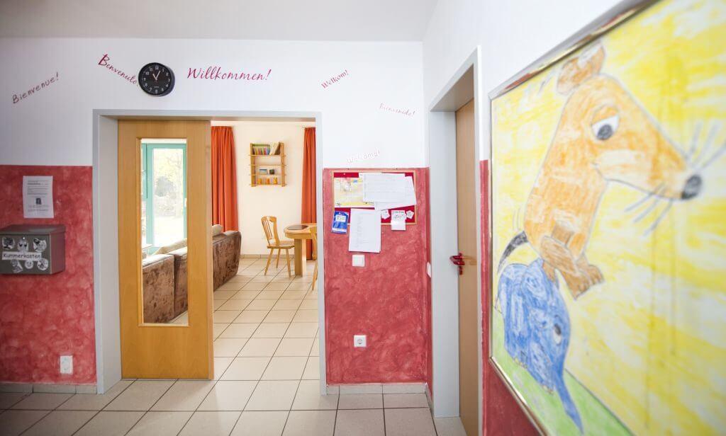 Innenaufnahme der Wohngruppe Wimmer mit Kummerkasten, offener Tür in den WOhnraum und einer Zeichnung von der Maus und dem Elefanten an der Wand