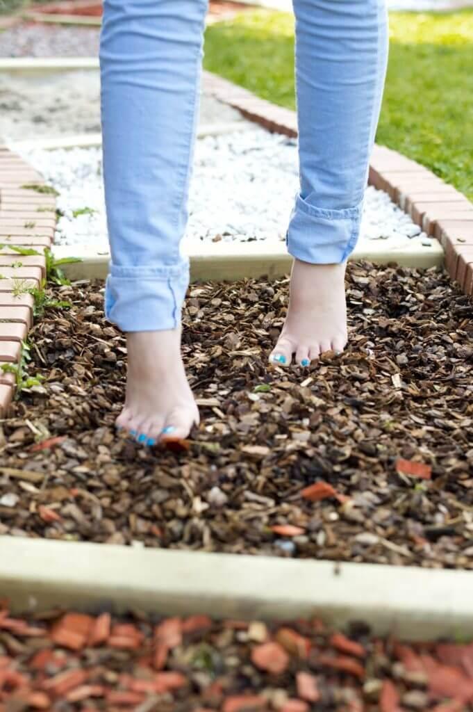 Mädchen mit blauer Hose läuft über Barfuß-Strecke