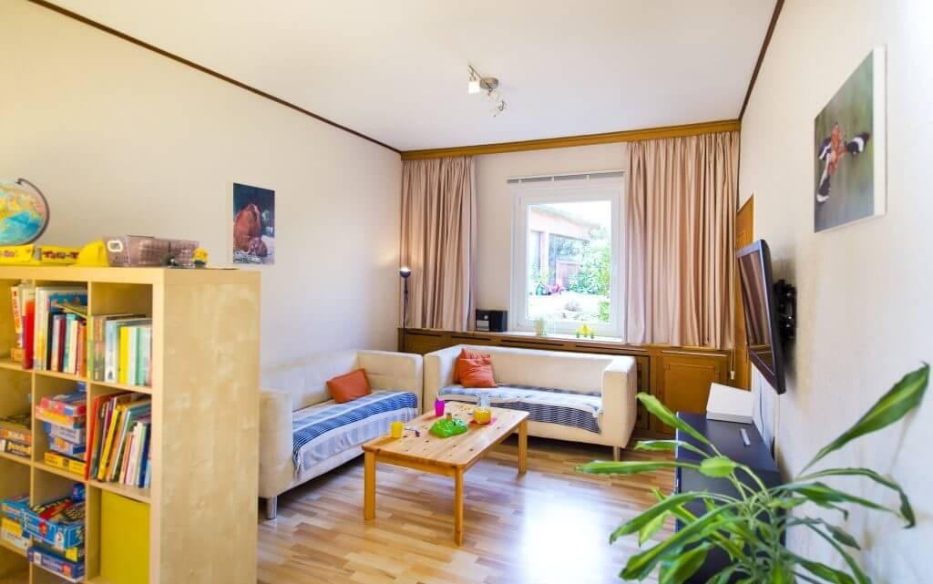 Heller Wohnbereich mit zwei Sofas und Fernseher und Spieleregal