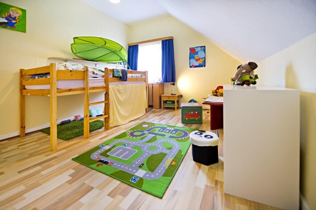 Zimmer mit Hochbett, Spielteppich und Regalen