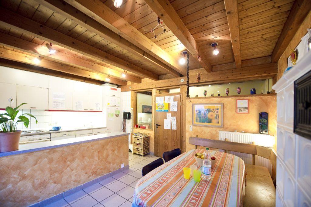Große Küche mit Holzdecke und Tresen und einer Sitzecke