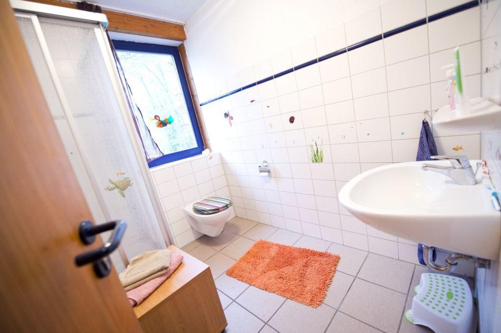 Helles Badezimmer mit Dusche, WC und Waschbecken