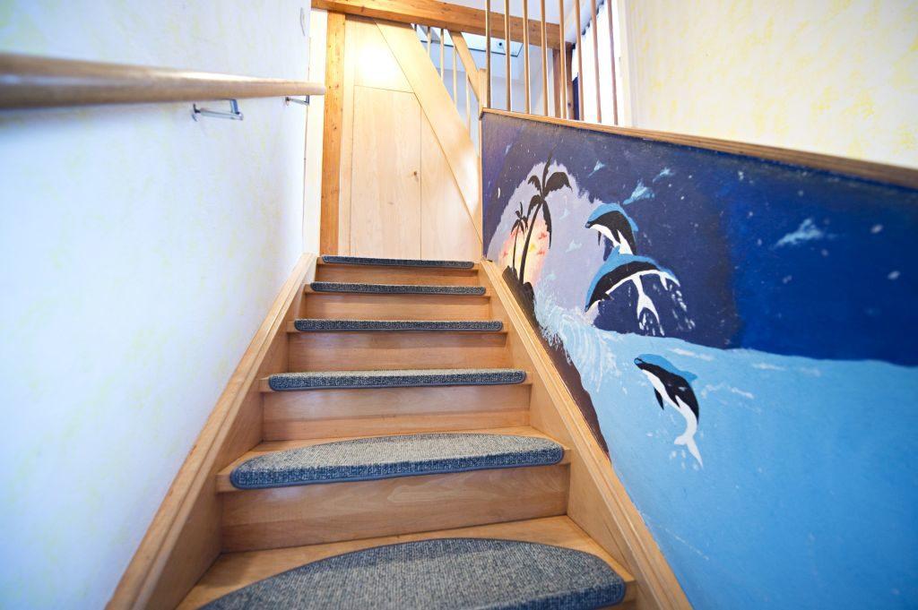 Treppenaufgang mit Delphinen und Sonnenuntergang an der Wand