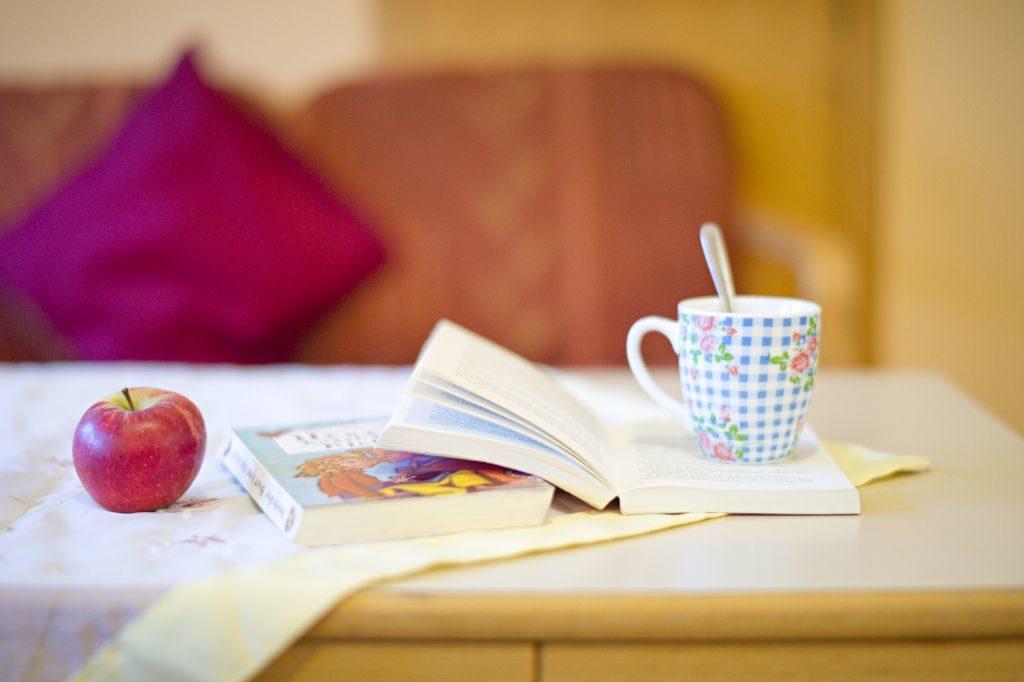 Ein aufgeschlagenes Buch mit einem warmen Getränk und einem Apfel