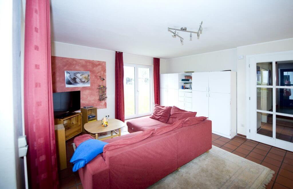 Heller Wohnraum mit rotem Ecksofa und Fernseher