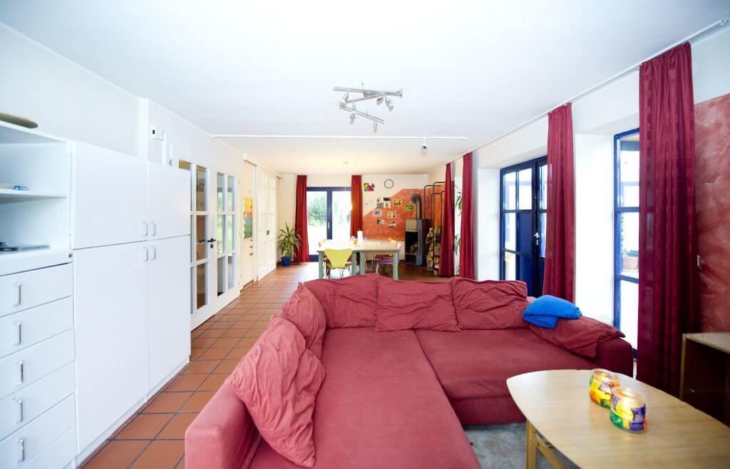 Heller Wohnraum mit rotem Sofa, Kamin und großem Tisch mit stühlen