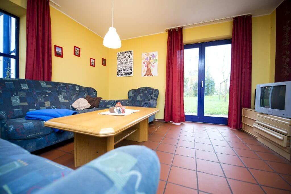 Gelber Wohnraum mit blauen Sofas und Fernseher