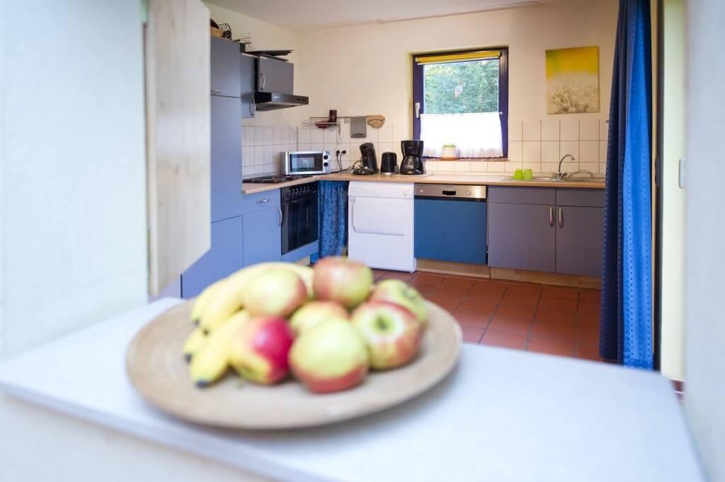 Blaue Küchenzeile mit Obststeller in der Durchreiche
