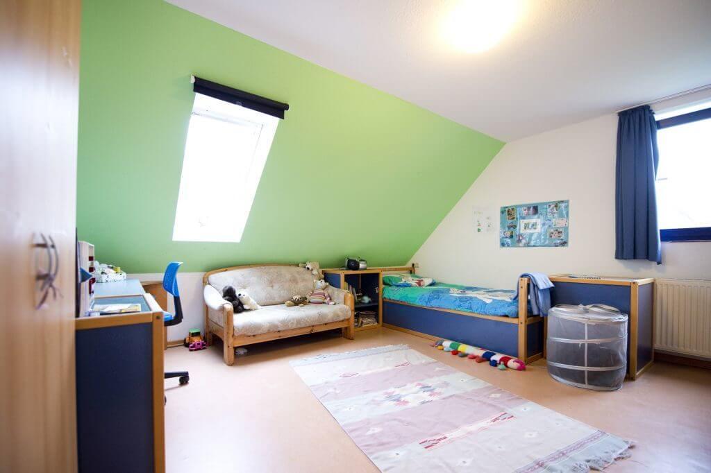 Helles Zimmer mit Bett und Sofa und Schreibtisch
