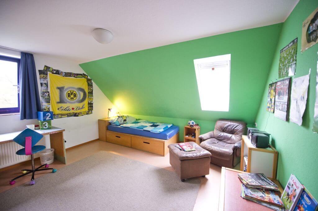 Ein Zimmer in grün und weiß gestrichen, mit Bett, Schreibtisch und Sessel und BVB Fanartikel geschmückt