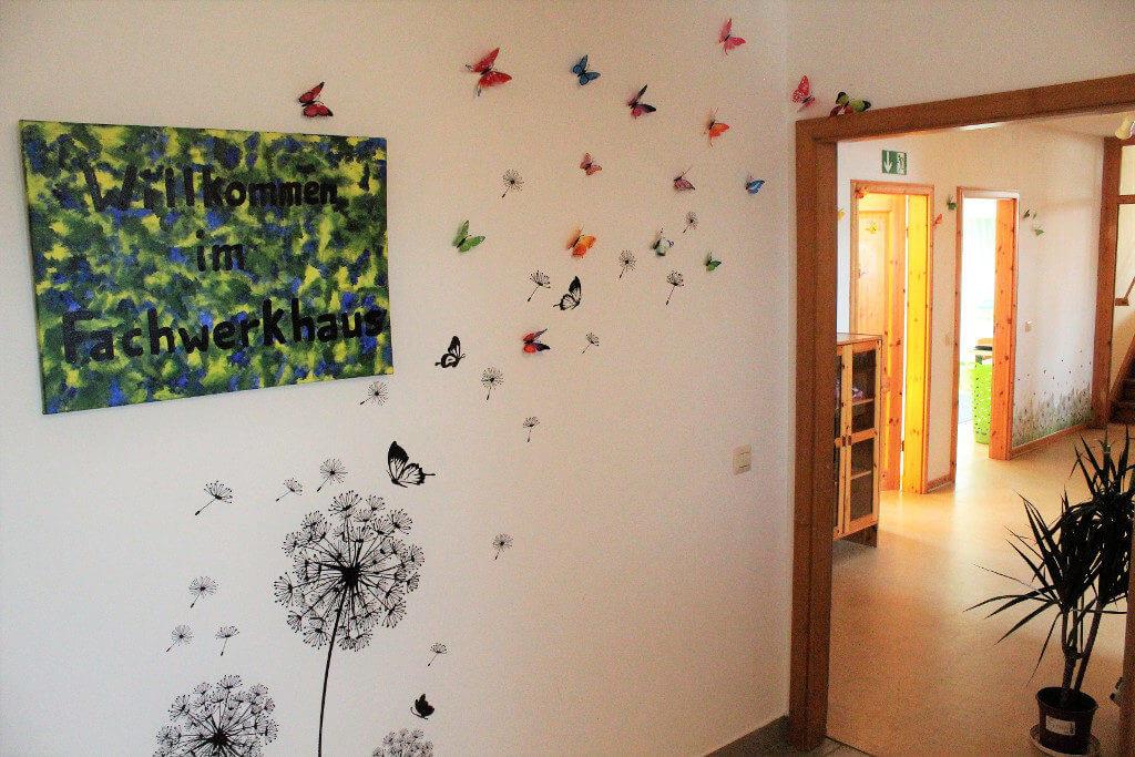 Eingangsbereich mit Willkommensleinwand und Pusteblumen mit Schmetterlingen an der Wand