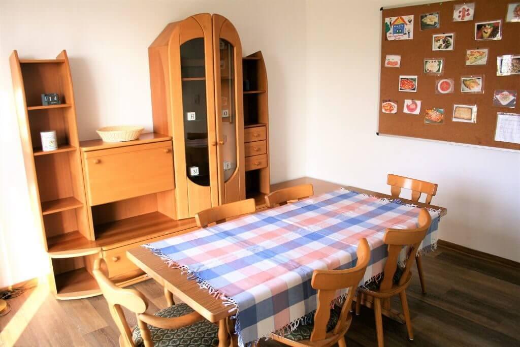 Essbereich mit Bildern von Gerichten an einer Pinnwand und Schrank an der Wand