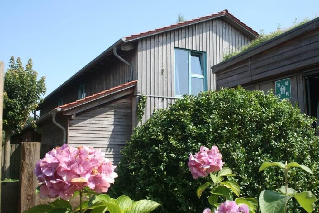 Außenansicht der Wohngruppe Wimmer mit Blumen im Vordergrund