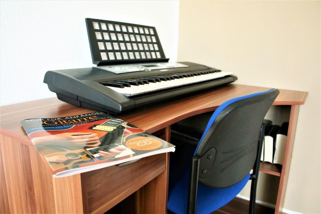 Ein Schreibtisch mit Keyboard und Gitarrenspielanleitung