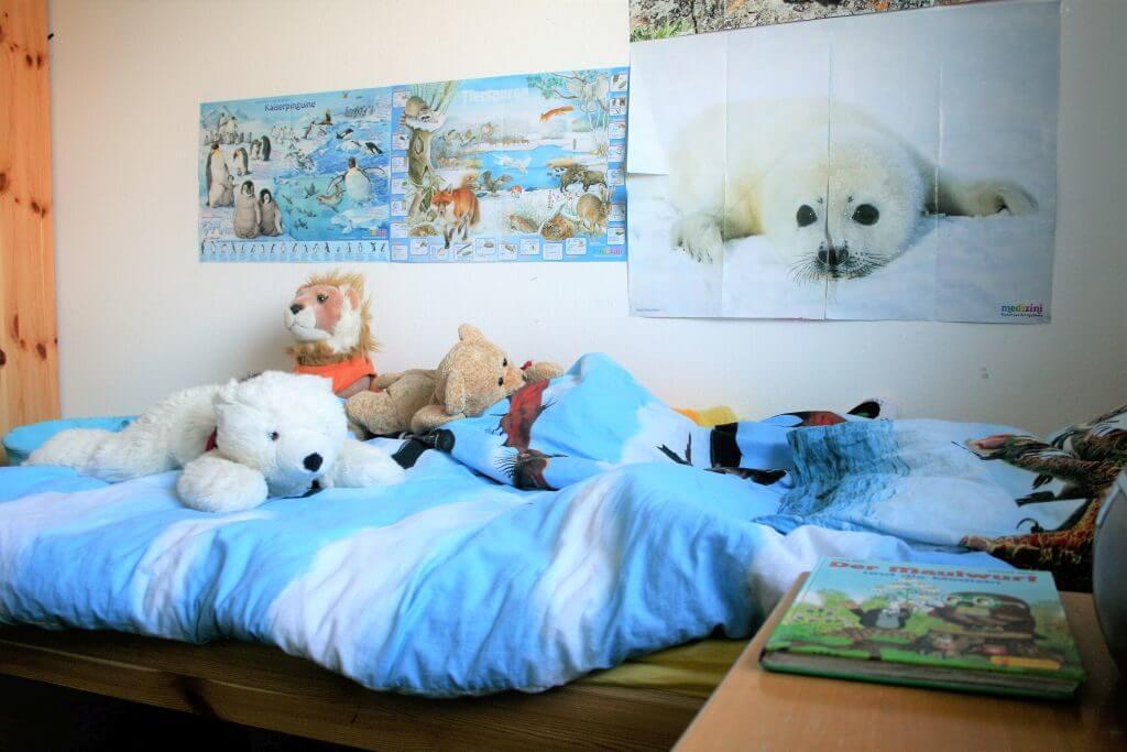 Kinderbett mit Kuscheltieren und Tierpostern an der Wand