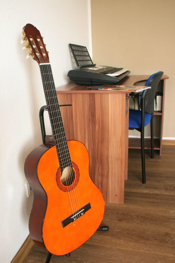 Schreibtisch mit Keyboard und davor eine Gitarre