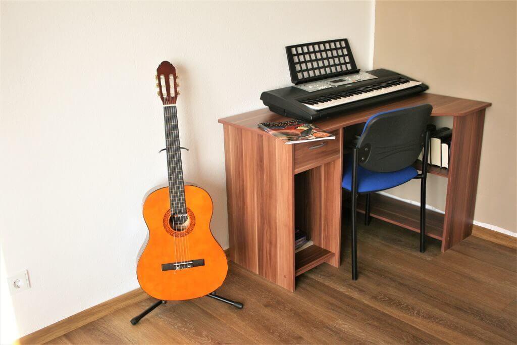 Schreibtisch mit Keyboard und daneben eine Gitarre