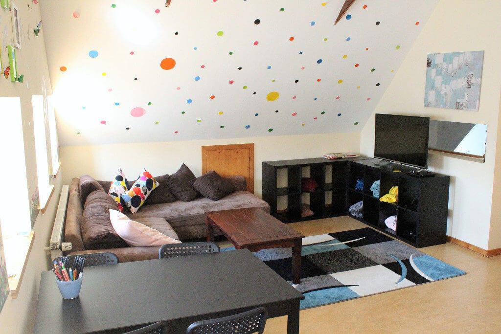 Zimmer im Punktedesign mit Ecksofa und Fernseher sowie Schreibtisch