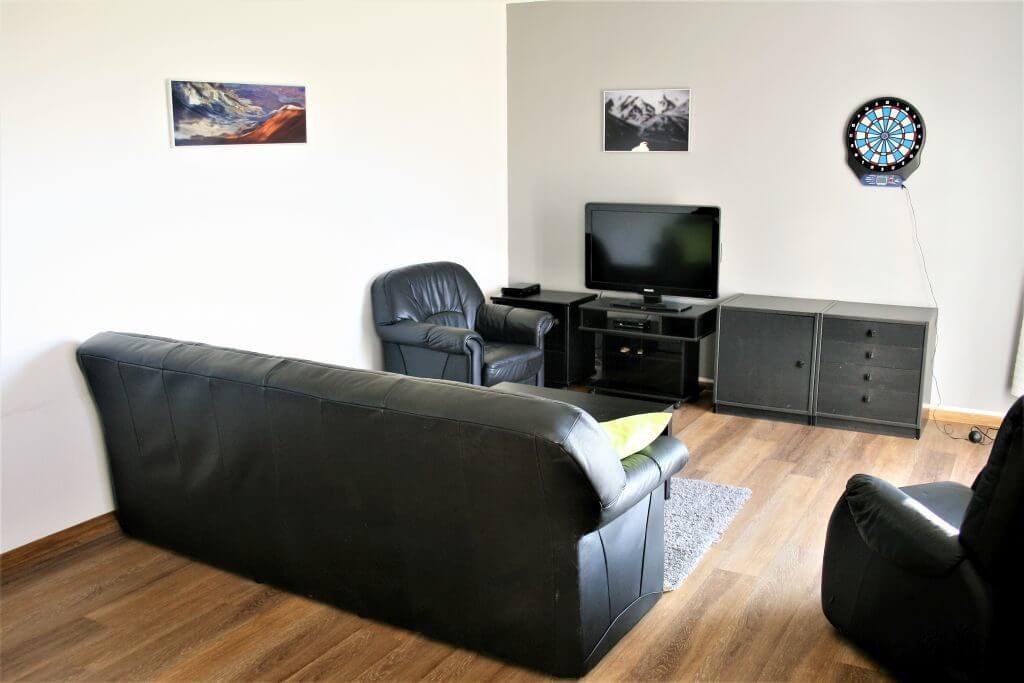 Wohnraum mit schwarzen Ledermöbeln und Fernseher
