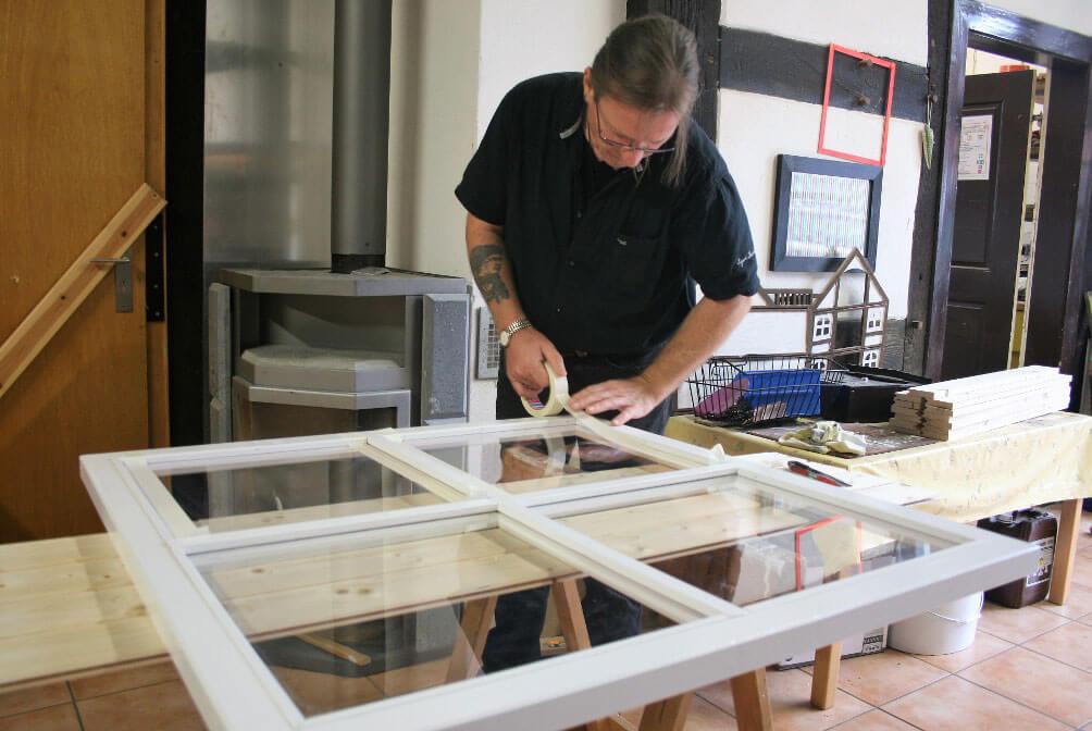 Ein Arbeitspädagoge klebt die Fensterscheiben eines Fensters vor dem Lackieren ab