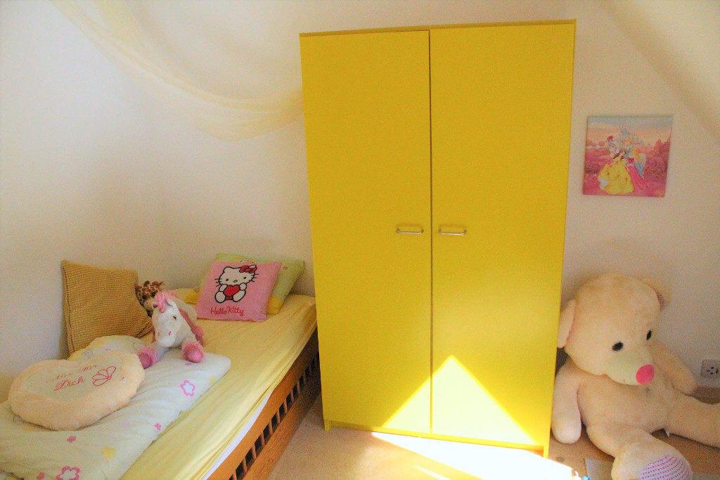 Kinderzimmer mit gelbem Schrank, Kuscheltieren und Prinzessinenleinwand
