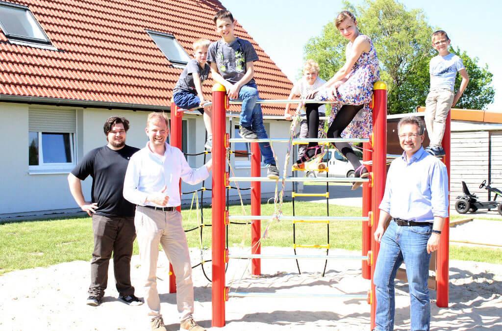 Gruppenfoto zur Einweihung des Klettergerüstes mit Kindern auf dem Gerüst und Erwachsenen unten