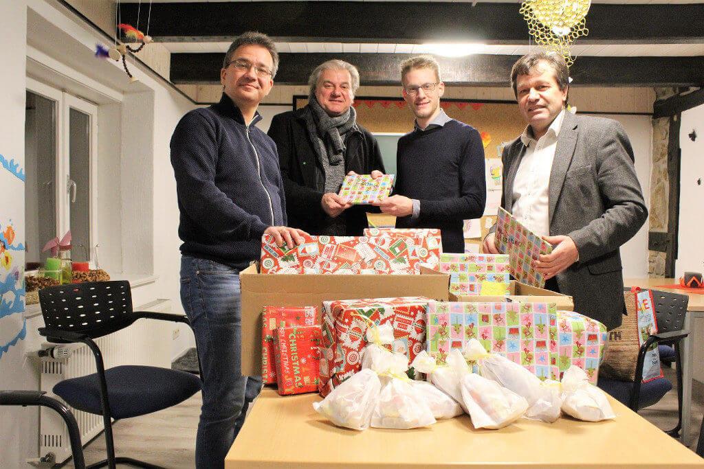 Gruppenfoto vom VSD und den LINKEN mit vielen Weihnachtspäckchen auf dem Tisch