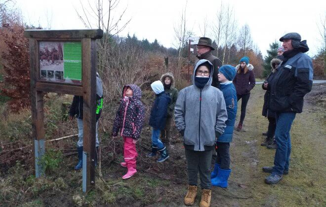 Eine Gruppe von Kindern und Erwachsenen erkunden im Herbst die Natur