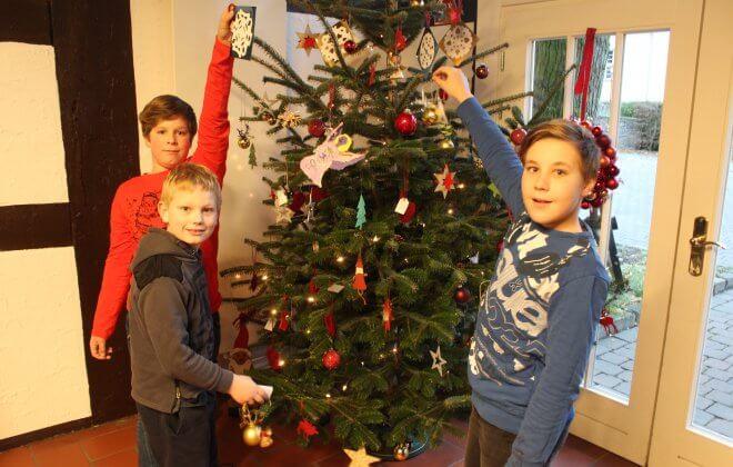 Drei Jungen hängen Anhänger an eine geschmückte Tanne
