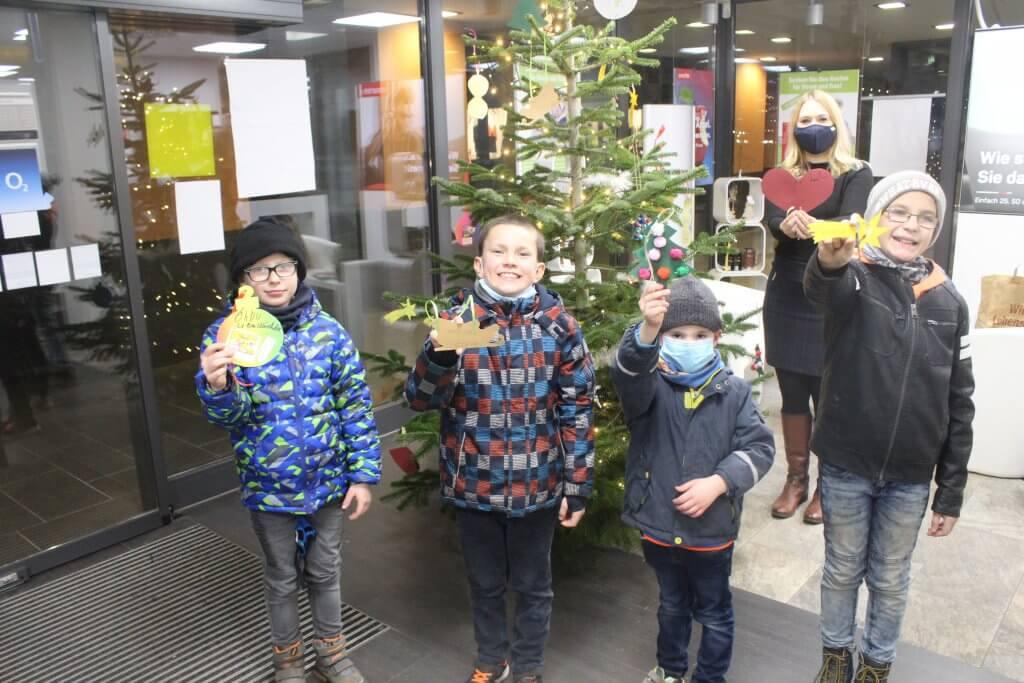 Vier Kinder stehen mit einem gebasteltem Anhänger vor einer geschmückten Tanne