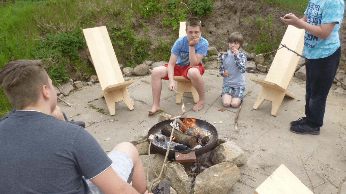 Eine Gruppe von Jungen sitzt an einer Feuerschale und röstet und isst Marshmallows